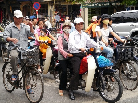 People on mopeds in an Asian city