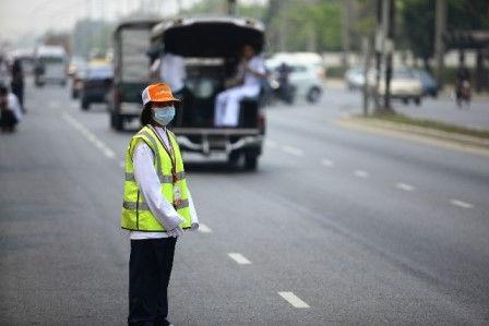person directing traffic wearing a face mask